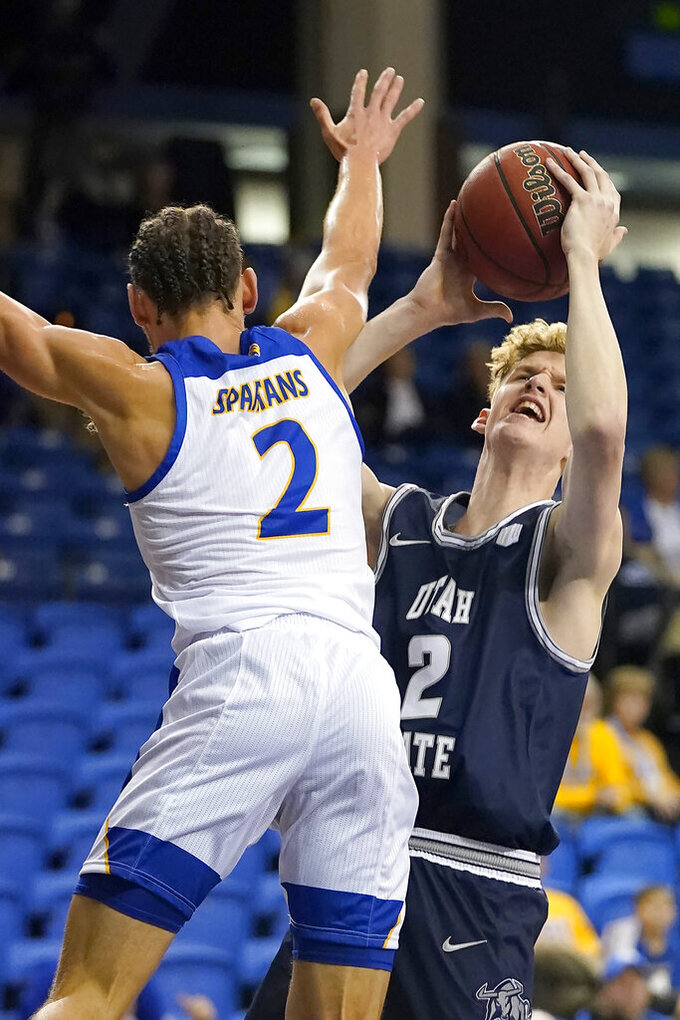 Utah State guard Sean Bairstow (2) reacts as he is fouled by San Jose State guard Brae Ivey (2) during the first half of an NCAA college basketball game Wednesday, Dec. 4, 2019, in San Jose, Calif. (AP Photo/Tony Avelar)