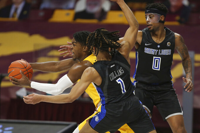 Minnesota's Marcus Carr (5) pushes the ball through the defense of Saint Louis' Yuri Collins (1) and Jordan Goodwin (0) during an NCAA college basketball game, Sunday, Dec. 20, 2020, in Minneapolis. Minnesota won 90-82. (AP Photo/Stacy Bengs)
