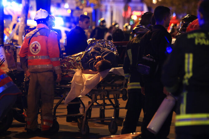 FILE - In this Nov;13, 2015 file photo, a person is being evacuated after a shooting, outside the Bataclan theater in Paris. France is putting on trial 20 men accused in the Nov. 13, 2015, Islamic State terror attacks on Paris that left 130 people dead and hundreds injured. (AP Photo/Thibault Camus, File)