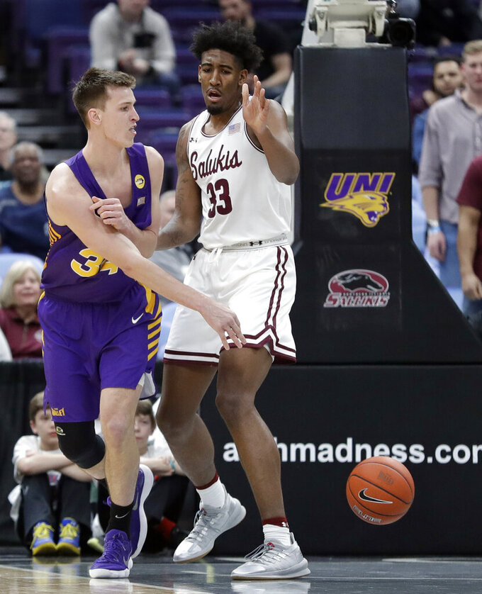 Northern Iowa's Luke McDonnell, left, passes around Southern Illinois' Kavion Pippen (33) during the first half of an NCAA college basketball game in the quarterfinal round of the Missouri Valley Conference tournament, Friday, March 8, 2019, in St. Louis. (AP Photo/Jeff Roberson)