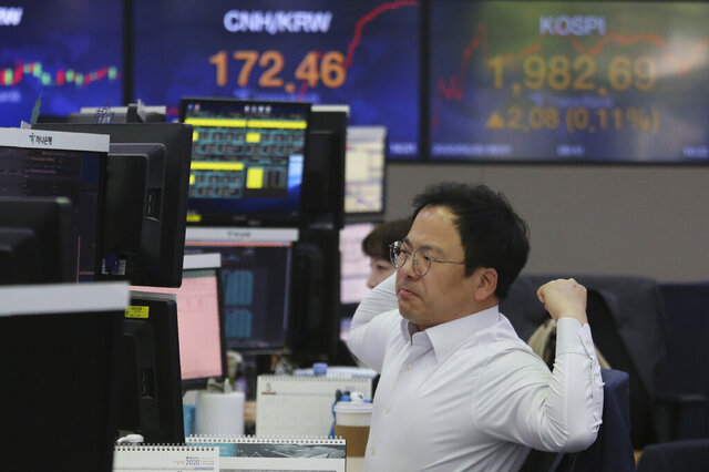 A currency trader watches monitors at the foreign exchange dealing room of the KEB Hana Bank headquarters in Seoul, South Korea, Wednesday, May 20, 2020.  Asian shares were mixed Wednesday as market players waffled between hopes for recovery as economies gradually reopen and worries over the havoc wreaked by the pandemic. (AP Photo/Ahn Young-joon)