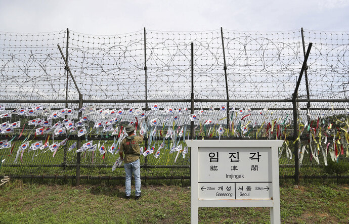 FILE - In this Aug. 13, 2017, file photo, A man adjusts national flags on wire fences near a directional sign showing the distance to North Korea's Kaesong city and South Korea's capital Seoul at the Imjingak Pavilion in Paju, South Korea. (AP Photo/Lee Jin-man, File)