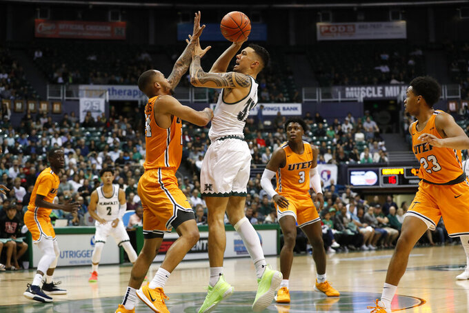 Hawaii guard Samuta Avea (32) shoots over UTEP guard Daryl Edwards (24) during the first half of an NCAA college basketball game Sunday, Dec. 22, 2019, in Honolulu. (AP Photo/Marco Garcia)
