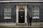 FILE - In this file photo dated Friday, June 7, 2019, a police officer stands guard outside the front door to the official residence of Britain's Prime Minister, 10 Downing Street, London.  Lawmakers are set to narrow the field of contenders for leadership of the Conservative Party and Prime Minister, in a series of elimination votes over the coming days from Monday June 17, 2019, with the final two names put to a vote of Conservative party members nationwide.  The six contenders to replace Prime Minister Theresa May are: Michael Gove, Jeremy Hunt, Sajid Javid, Boris Johnson, Dominic Raab, Rory Stewart. (AP Photo/Matt Dunham, FILE)