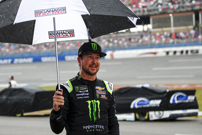 Kurt Busch walks back to garage during a rain delay at a NASCAR Cup Series auto race at Talladega Superspeedway in Talladega, Ala., Sunday, Oct. 13, 2019. (AP Photo/Butch Dill)