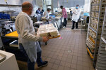 Volunteers prepare meals at Community Servings, which prepares and delivers scratch-made, medically tailored meals to individuals & families living with critical & chronic illnesses, Tuesday, Jan. 12, 2021, in the Jamaica Plain neighborhood of Boston. Food is a growing focus for insurers as they look to improve the health of the people they cover and cut costs. Insurers first started covering Community Servings meals about five years ago, and CEO David Waters says they now cover close to 40%. (AP Photo/Charles Krupa)