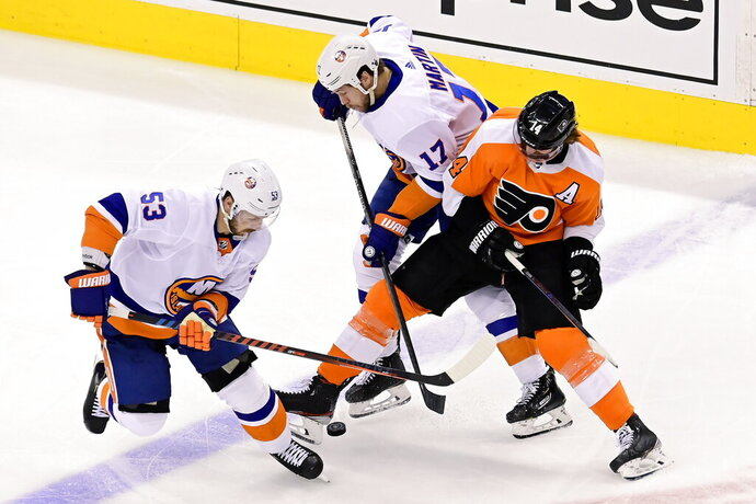 Philadelphia Flyers center Sean Couturier (14) tries to hold onto the puck under pressure from New York Islanders center Casey Cizikas (53) and teammate Matt Martin (17) during the second period of an NHL Stanley Cup Eastern Conference playoff hockey game in Toronto, Ontario, Tuesday, Sept. 1, 2020. (Frank Gunn/The Canadian Press via AP)