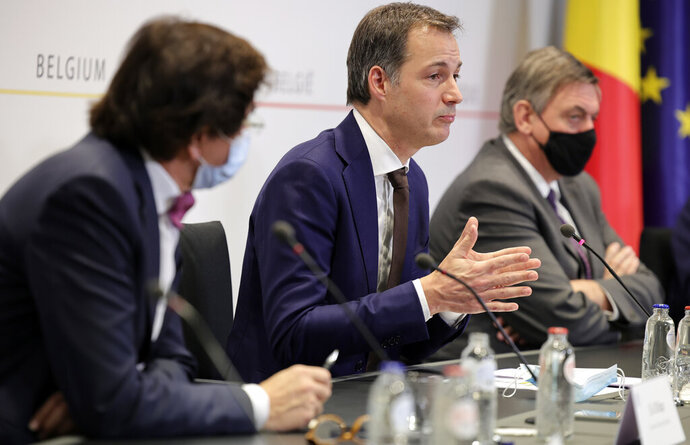 Belgium's Prime Minister Alexander De Croo, center, speaks during a news conference following a government meeting on the coronavirus, COVID-19, in Brussels, Friday, Nov. 27, 2020. (AP Photo/Olivier Matthys, Pool)