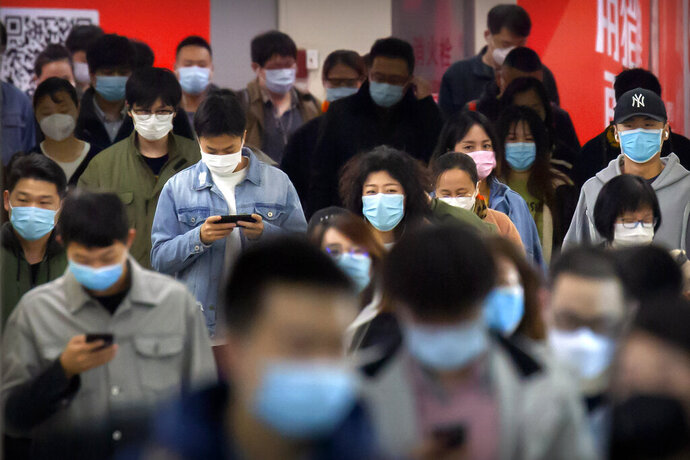 Commuters wear face masks to protect against the spread of new coronavirus as they walk through a subway station in Beijing, Thursday, April 9, 2020. China's National Health Commission on Thursday reported dozens of new COVID-19 cases, including most of which it says are imported infections in recent arrivals from abroad and two