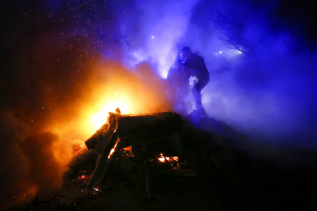 A protester, who planned to stop buses carrying passengers evacuated from the Chinese city of Wuhan, kindles a fire outside Novi Sarzhany, Ukraine, Thursday, Feb. 20, 2020. Several hundred residents in Ukraine's Poltava region protested to stop officials from quarantining the evacuees in their village because they feared becoming infected. Demonstrators put up road blocks and burned tires, while Ukrainian media reported that there were clashes with police, and more than 10 people were detained. (AP Photo/Efrem Lukatsky)