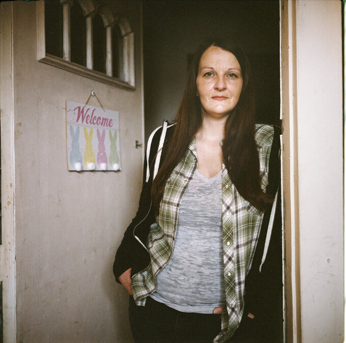 "In this photo made with a medium format film camera, Sarah Kelly, 37, stands in the doorway of her home in Guyandotte, W.Va., Wednesday, March 17, 2021. After struggling with opioid addiction most of her life, Kelly white-knuckled her way through the pandemic. Then she navigated courts to get custody of her kids back after more than two years apart. Kelly's younger sister died from a heart infection from injection drug use in 2017, and her own addiction spiraled as she tried to numb herself from guilt and despair. ""I knew there was this version of me still in there somewhere, and I knew that if I woke up every day and really decided to stay sober, I could get to be her again,"" she said. ""I could look in the mirror and be proud of who I was, and my children could be proud of me."" They live together now in a little house on the outskirts of town. (AP Photo/David Goldman)"