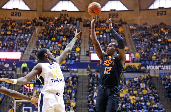 Oklahoma State forward Cameron McGriff (12) shoots over West Virginia forward Lamont West (15) during the first half of an NCAA college basketball game Saturday, Jan. 12, 2019, in Morgantown, W.Va. (AP Photo/Raymond Thompson)