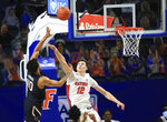 South Carolina forward Justin Minaya (10) makes a shot over Florida forward Colin Castleton (12) during the first half of an NCAA college basketball game Wednesday, Feb. 3, 2021, in Gainesville, Fla. (AP Photo/Matt Stamey)