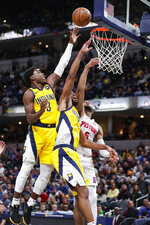 Detroit Pistons guard Bruce Brown (6) and Indiana Pacers guard Aaron Holiday (3) and forward T.J. Warren (1) go up for a rebound during the second half of an NBA basketball game in Indianapolis, Friday, Nov. 8, 2019. The Pacers won 112-106. (AP Photo/Michael Conroy)