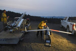 In this Tuesday, Aug. 7, 2018 photo, Ty Sibley, right, an unmanned aircraft system operator for Insitu, prepares a ScanEagle drone on a ridge south of Galesville Reservoir near Azalea, Ore. The aircraft, equipped with an infrared camera, flew for more than seven hours that night while detecting hotspots over the Taylor Creek Fire in Southwest Oregon. (Scott Stoddard/The Daily Courier via AP)