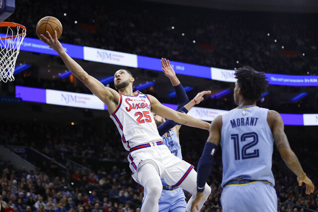 Philadelphia 76ers' Ben Simmons, left, goes up for a shot against Memphis Grizzlies' Jonas Valanciunas, center, and Ja Morant during the first half of an NBA basketball game Friday, Feb. 7, 2020, in Philadelphia. (AP Photo/Matt Slocum)