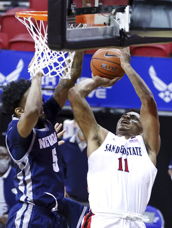 San Diego State forward Matt Mitchell (11) shoots as Nevada forward Warren Washington (5) defends during the first half of an NCAA college basketball game in the semifinal round of the Mountain West Conference men's tournament Friday, March 12, 2021, in Las Vegas. (AP Photo/Isaac Brekken)