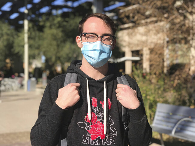 Arizona State University student Chase Hales wears a mask while on campus in Tempe, Ariz., on Tuesday, Jan. 28, 2020. A confirmed case of a virus outbreak from China at Arizona State University has left students feeling alarmed, despite the school's attempts to tamp down panic. (Griselda Zetino/KTAR News 92.3 via AP)