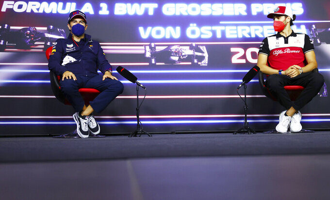 Red Bull driver Sergio Perez of Mexico, left, and Alfa Romeo driver Antonio Giovinazzi of Italy attend a media conference ahead of the Austrian Formula One Grand Prix at the Red Bull Ring racetrack in Spielberg, Austria, Thursday, July 1, 2021. (Dan Istitene/Pool Photo via AP)