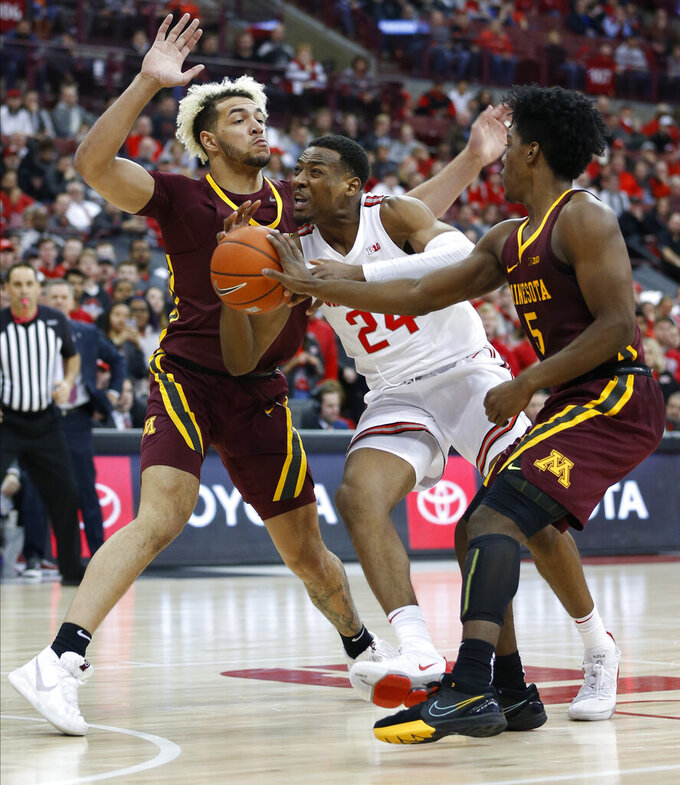 Ohio State's Andre Wesson, center, tries to dribble between Minnesota's Jarvis Omersa, left, and Marcus Carr during the second half of an NCAA college basketball game Thursday, Jan. 23, 2020, in Columbus, Ohio.  (AP Photo/Jay LaPrete)