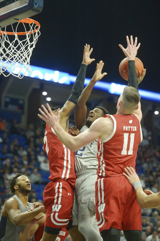 Penn State's Izaiah Brockington (12) splits Wisconsin defenders Aleem Ford (left) and Lamar Stevens (11) during first half action of an NCAA college basketball game, Saturday, Jan. 11, 2020, in State College, Pa. (AP Photo/Gary M. Baranec)
