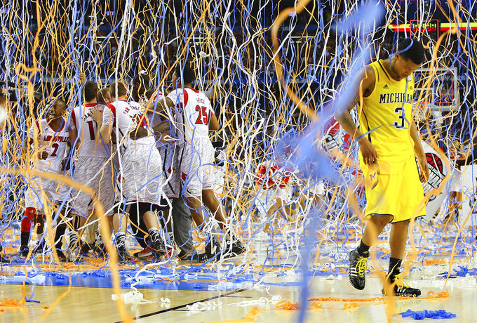 FILE - In this April 8, 2013, file photo, Michigan guard Trey Burke (3) walks off the court as confetti falls on Louisville players, including Russ Smith (2), Luke Hancock (11), Stephan Van Treese (44) and Zach Price (25), after the NCAA Final Four tournament college basketball championship game in Atlanta. Coronavirus stopped March Madness before it could begin, meaning there would be no men's national college basketball tournament and no championship game. The virus also silenced another long-standing tradition, but Max Goren refused to let that tradition die.  (AP Photo/Atlanta Journal-Constitution, Curtis Compton, File)