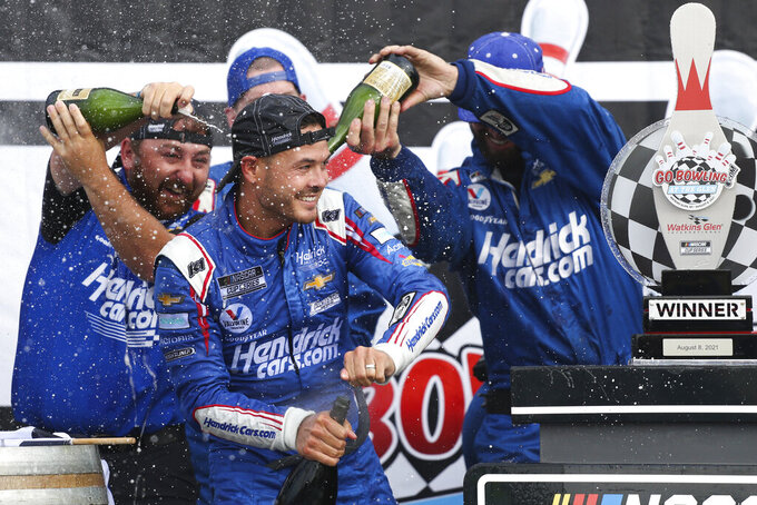 Kyle Larson, center, celebrates with his pit crew after winning a NASCAR Cup Series auto race in Watkins Glen, N.Y., on Sunday, Aug. 8, 2021. (AP Photo/Joshua Bessex)