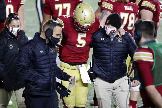 Boston College quarterback Phil Jurkovec (5) is helped off the field beside head coach Jeff Hafley, second from left, during the second half of an NCAA college football game against Louisville, Saturday, Nov. 28, 2020, in Boston. (AP Photo/Michael Dwyer)