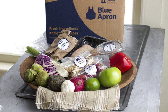 FILE - This Oct. 6, 2014, file photo shows an example of a home-delivered meal from Blue Apron, in Concord, N.H. Meal kit companies face an ultimatum: Adapt or die. The struggle has intensified for Blue Apron, which announced that it could be delisted from the New York Stock Exchange because its closing share price has been lower than $1 since early May 2019. (AP Photo/Matthew Mead, File)