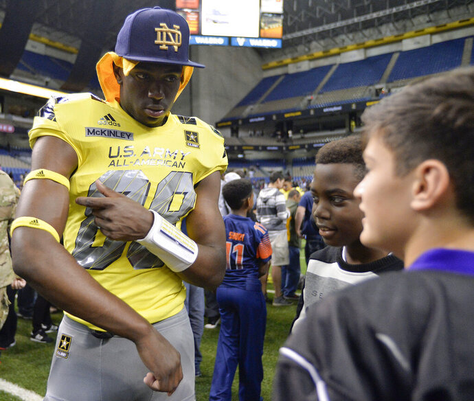 In this Jan. 9, 2016, file photo, wide receiver Javon McKinley, left, gives his armbands to a fan after the Army All American Bowl high school football game in San Antonio. Notre Dame redshirt sophomore receiver Javon McKinley faces misdemeanor battery and illegal consumption of alcohol charges in connection with an assault on two campus officers. The Indianapolis Star reports Monday, Feb. 11, 2019, from court documents that McKinley was unresponsive about 4 a.m. Sunday in an Uber vehicle and the officers were punched while trying to help him to his dorm at the South Bend, Indiana, school. The document says the officers reportedly said they smell alcohol on McKinley's breath. (AP Photo/Darren Abate)