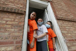 Mariano Ochoa, 9, left, poses for photo with his brothers Victor Ochoa, 7, center, Jesus Ochoa, 5, at their home in Chicago, Friday, May 22, 2020. Mariana Ochoa has three young boys, ages 9, 7, and 5, and Chicago Run's at-home fitness programs have become an essential part of the family's routine during the coronavirus pandemic. (AP Photo/Nam Y. Huh)