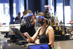 Bartenders were masks and face shields as they work at Slater's 50|50 in Wednesday, July 1, 2020, in Santa Clarita, Calif. California Gov. Gavin Newsom has ordered a three-week closure of bars, indoor dining and indoor operations of several other types of businesses in various counties, including Los Angeles, as the state deals with increasing coronavirus cases and hospitalizations. (AP Photo/Marcio Jose Sanchez)