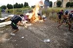 Squatters set fire to a barricade created outside an abandoned school before being evicted, on the outskirts of Rome, Monday, July 15, 2019. Residents set fire early Monday to mattresses and other garbage to form a barrier and prevent riot police from entering the building but authorities doused the blaze and proceeded with the eviction. (Massimo Percossi/ANSA via AP)