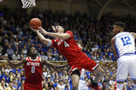 North Carolina State forward Jericole Hellems (4) drives past Duke forward Javin DeLaurier (12) for a shot during the first half of an NCAA college basketball game in Durham, N.C., Monday, March 2, 2020. North Carolina State forward D.J. Funderburk (0) looks on. (AP Photo/Gerry Broome)