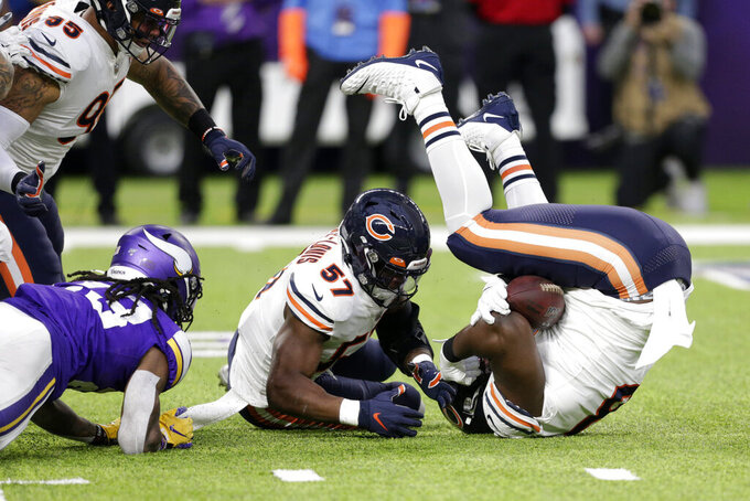 Chicago Bears defensive tackle Bilal Nichols, right, and linebacker Kevin Pierre-Louis (57) recover a fumble by Minnesota Vikings running back Mike Boone, left, during the first half of an NFL football game, Sunday, Dec. 29, 2019, in Minneapolis. (AP Photo/Andy Clayton-King)