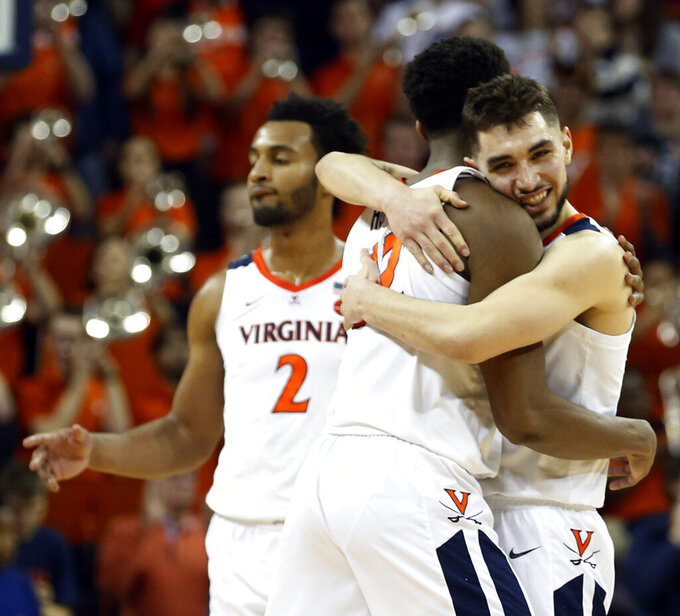 Virginia guard Ty Jerome, right, hugs Virginia guard De'Andre Hunter after an NCAA college basketball game against Louisville in Charlottesville, Va., Saturday, March 9, 2019. (AP Photo/Steve Helber)