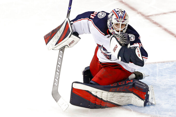 THIS CORRECTS THAT KIVLENIEKS DIED OF CHEST TRAUMA FROM AN ERRANT FIREWORKS MORTAR BLAST AND NOT A SUBSEQUENT FALL AS AUTHORITIES PREVIOUSLY REPORTED - FILE - Columbus Blue Jackets goaltender Matiss Kivlenieks (80) has the puck in his hand as he makes a save during the third period of an NHL hockey game against the New York Rangers in New York, in this Sunday, Jan. 19, 2020, file photo. The Columbus Blue Jackets and Latvian Hockey Federation said Monday, July 5, 2021, that 24-year-old goaltender Matiss Kivlenieks has died. A medical examiner in Michigan says an autopsy has determined that Columbus Blue Jackets goaltender Matiss Kivlenieks died of chest trauma from an errant fireworks mortar blast, and not a fall as authorities previously reported. Police in Novi, Michigan, said the mortar-style firework tilted slightly and started to fire toward people nearby Sunday night, July 4. (AP Photo/Kathy Willens, File)