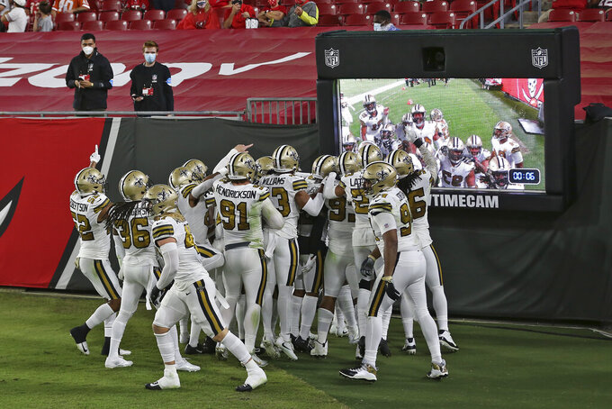 New Orleans Saints players celebrate in front of a video feed after defensive tackle David Onyemata intercepted a pass by Tampa Bay Buccaneers quarterback Tom Brady during the first half of an NFL football game Sunday, Nov. 8, 2020, in Tampa, Fla. (AP Photo/Mark LoMoglio)