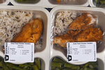 Freshly made meals, with dietary labels, are packaged for clients at Community Servings, which prepares and delivers scratch-made, medically tailored meals to individuals & families living with critical & chronic illnesses, Tuesday, Jan. 12, 2021, in the Jamaica Plain neighborhood of Boston. Food is a growing focus for insurers as they look to improve the health of the people they cover and cut costs. Insurers first started covering Community Servings meals about five years ago, and CEO David Waters says they now cover close to 40%. (AP Photo/Charles Krupa)