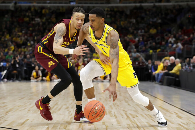 Michigan's Charles Matthews (1) drives against Minnesota's Amir Coffey during the second half of an NCAA college basketball game in the semifinals of the Big Ten Conference tournament, Saturday, March 16, 2019, in Chicago. (AP Photo/Nam Y. Huh)