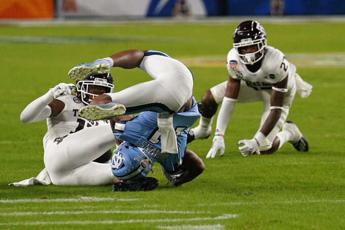 North Carolina wide receiver Josh Downs (11) falls on his head after he was tripped by Texas A&M defensive back Antonio Johnson (27), during the first half of the Orange Bowl NCAA college football game Saturday, Jan. 2, 2021, in Miami Gardens, Fla. (AP Photo/Marta Lavandier)