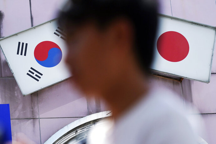 In this Aug. 13, 2019 photo, a man walks past an advertisement featuring Japanese and South Korean flags at a shop in Shin Okubo area, in Tokyo. South Korea and Japan have locked themselves in a highly-public dispute over history and trade that in a span of weeks saw their relations sink to a low unseen in decades. This area is known for Korean restaurants and stores selling K-pop merchandise.(AP Photo/Eugene Hoshiko)