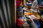 Elena, 7, center, lines up with other displaced Tigrayans to receive food donated by local residents at a reception center for the internally displaced in Mekele, in the Tigray region of northern Ethiopia, on Sunday, May 9, 2021. (AP Photo/Ben Curtis)