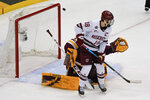 A puck shot by Massachusetts' Zac Jones whizzes past Jake Gaudet (18) and Minnesota Duluth goaltender Zach Stejskal for a goal during the first period of an NCAA men's Frozen Four hockey semifinal in Pittsburgh, Thursday, April 8, 2021. (AP Photo/Keith Srakocic)