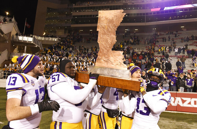 LSU players Andre Sale (13), Chasen Hines (57) and Jontre Kirklin, right, help carry off the Boot trophy after beating Arkansas 24-17 during an NCAA college football game, Saturday, Nov. 10, 2018, in Fayetteville, Ark. (AP Photo/Michael Woods)