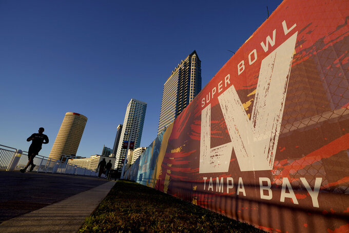 A man passes signage for Super Bowl 55 as he runs along the Hillsborough River on Wednesday, Feb. 3, 2021, in Tampa, Fla. The city is hosting Sunday's Super Bowl football game between the Tampa Bay Buccaneers and the Kansas City Chiefs. (AP Photo/Charlie Riedel)
