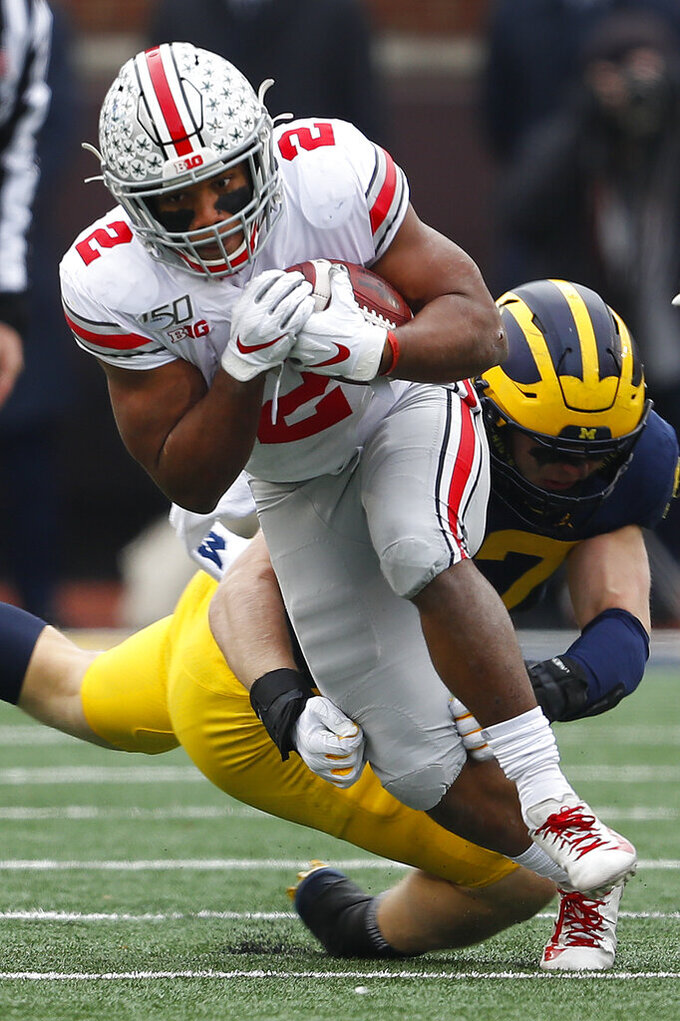 Ohio State running back J.K. Dobbins (2) escapes the tackle of Michigan defensive lineman Aidan Hutchinson (97) in the first half of an NCAA college football game in Ann Arbor, Mich., Saturday, Nov. 30, 2019. (AP Photo/Paul Sancya)