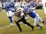 Miami's Cam'Ron Harris (23) runs upfield against Duke defenders Trevon McSwain (95) and Tre Hornbuckle (59) during the first quarter of NCAA college football game in Durham, N.C., Saturday, Nov. 30, 2019. (AP Photo/Chris Seward)