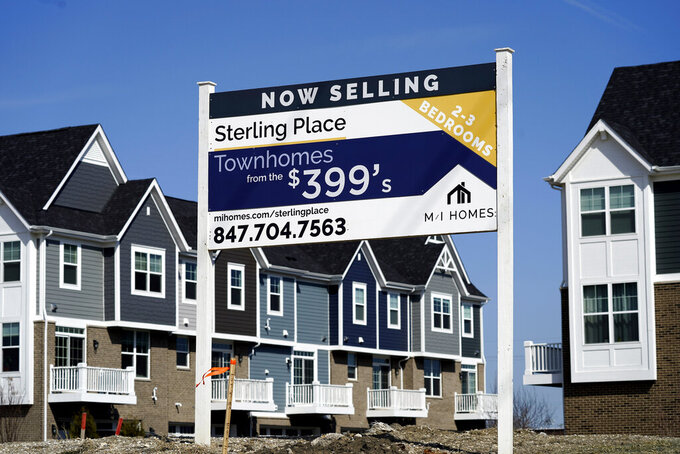 FILE - This March 21, 2021 photo shows an advertising sign for building land stands in front of a new home construction site in Northbrook, Ill.  Soaring home prices and rents are fueling real estate companies' appetite for houses, adding unwelcome competition for many would-be homebuyers.  (AP Photo/Nam Y. Huh)