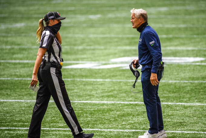 FILE - In this Sept. 13, 2020, file photo, Seattle Seahawks coach Pete Carroll talks with line judge Sarah Thomas during the first half of the team's NFL football game against the Atlanta Falcons in Atlanta. For the first time in NFL history, there will be two female coaches on the sideline and a female official on the field when the Browns host the Washington Football team. Jennifer King is in her first season on Washington's staff while Callie Brownson is the chief of staff for Browns first-year coach Kevin Stefanski. Thomas became the league's first female official in 2015, has worked in the postseason and is now making more history. (AP Photo/Danny Karnik, File)